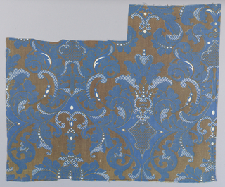 All-over vertically symmetrical pattern of scrolling leaves forming large ogee lattice in a rococo style, in brown and white on a dark blue background. Two pieces overlapped form full pattern.
