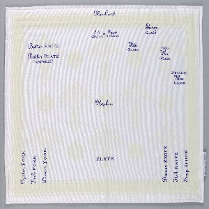 Rectangular white placemat with a subtle pattern of pale yellow fleur-de-lis in the background, overprinted in purple with instructions for the placement of the plates, glasses, and flatware.