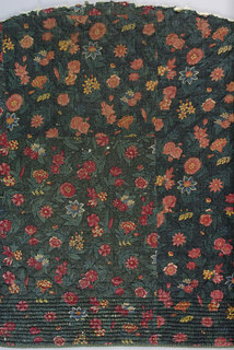 Fragment of a quilted fabric with a design of small-scale floral sprigs in bright colors on a dense green leafy pattern on a black ground. Quilting at bottom is a border of narrow ribs.