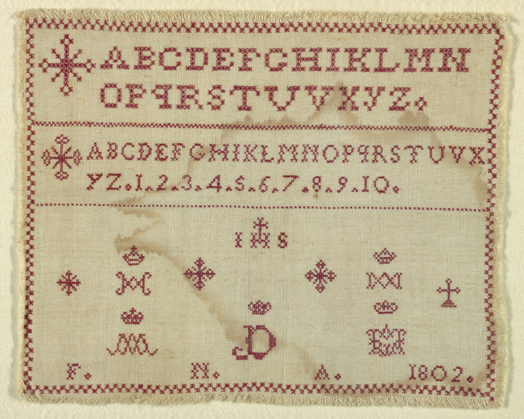Two alphabets introduced by a Maltese cross. Lower field is religious motifs all in red on natural.