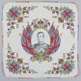 "Commemorative handkerchief showing a crowned portrait of Edward, Prince of Wales in military uniform with orders, flags on either side and a ribbon inscribed with ""Long Live Edward VIII Emperor"" below. In each corner: a shield with the Union Flag, scepters and floral sprays of rose, thistle, shamrock and leek. Printed in black, red, blue, green and yellow."