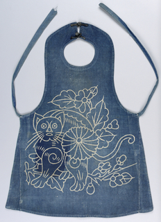 Child's bib with a design of a very stylized cat and flower arrangement in off-white on blue background.