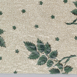 """Cotton, with cream color background, roller printed in small all-over pattern of vine and dotted ground in brown. Over-printed, probably by blocks in detached pattern of leaf sprays in strong green. The green is chemical or """"direct"""" green. Glazed."""