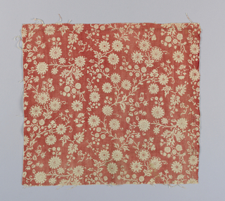 Fragment with an orange-red ground with a design of branching flower sprays reserved in white.