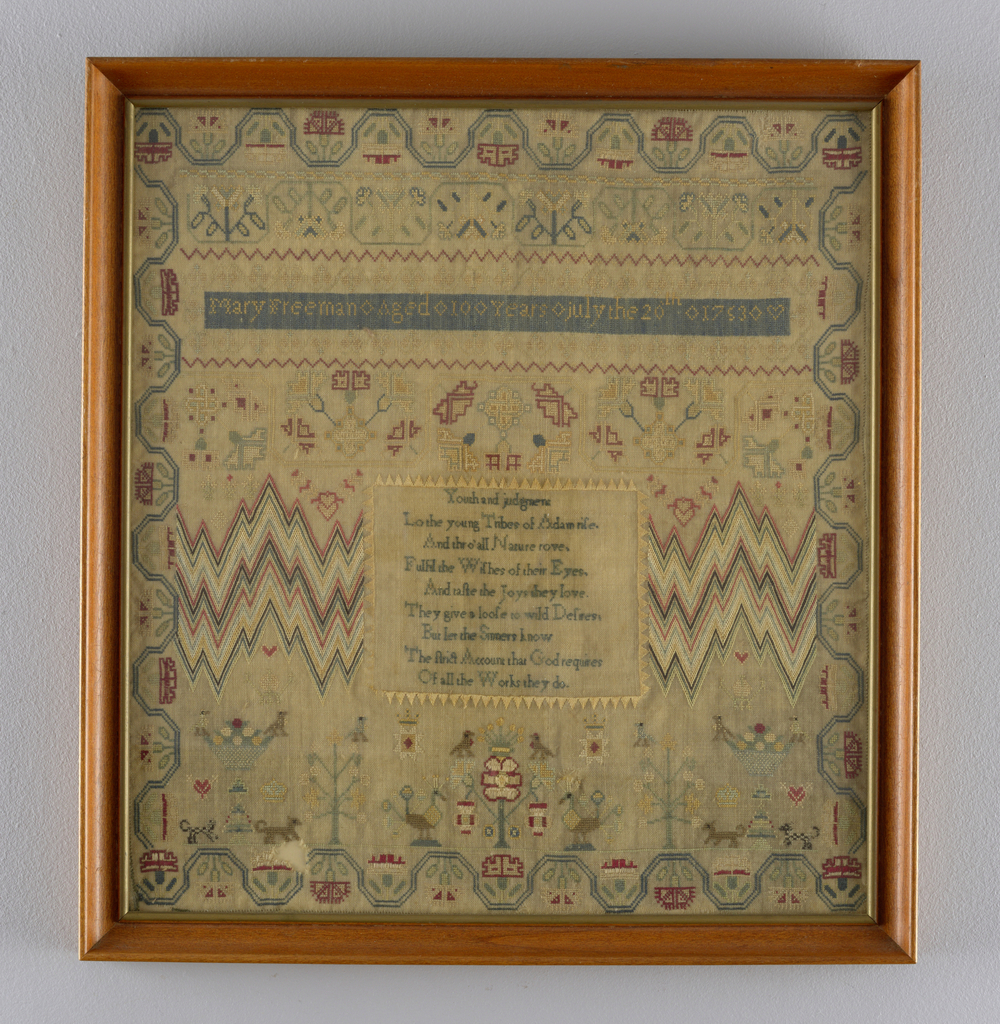 """Very finely worked in colored silk on a fine natural linen ground.  Running vine border, bargello panels, and a verse, """"Youth and judgement."""""""