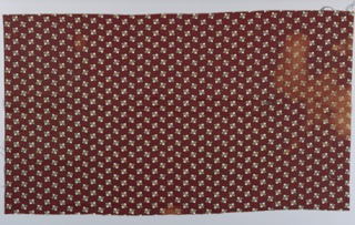 Offset repeat of a small allover stylized leaf pattern in reddish brown, tan and black on a white ground.