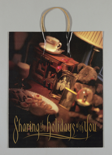 """Marshall Field's Sharing the Holiday with You.""  Color  photo of cookies, teddy bear, cup and glass. In red side panels: store name and text, ""The holidays are a time for sharing... ."""