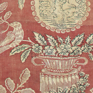 Design shows a basket of flowers with birds on a short fluted column and medallions with a Cupid-like figure and a goat. Design is in white on a red ground with flowers printed in dark brown.
