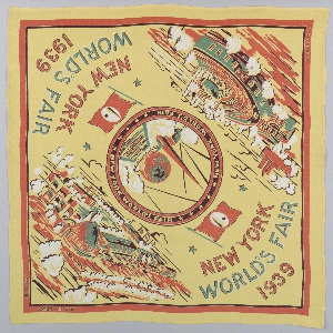 """Souvenir handkerchief issued on the occasion of the 1939 World's Fair in New York. In the center medallion is a view of the Trylon and Perisphere; in two corners are  aerial views of the Flushing Meadows site; and in the two alternate corners """"New York World's Fair 1939"""" with the fair flag featuring the Trylon and Persphere. Printed in orange, green and brown on a yellow ground."""