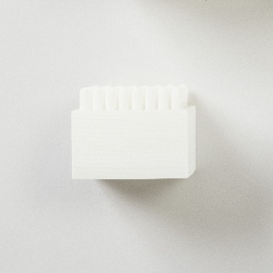 Fifty-seven small, differently shaped connectors of translucent white 3D-printed plastic made to link diverse parts from a variety of construction sets by different manufacturers.