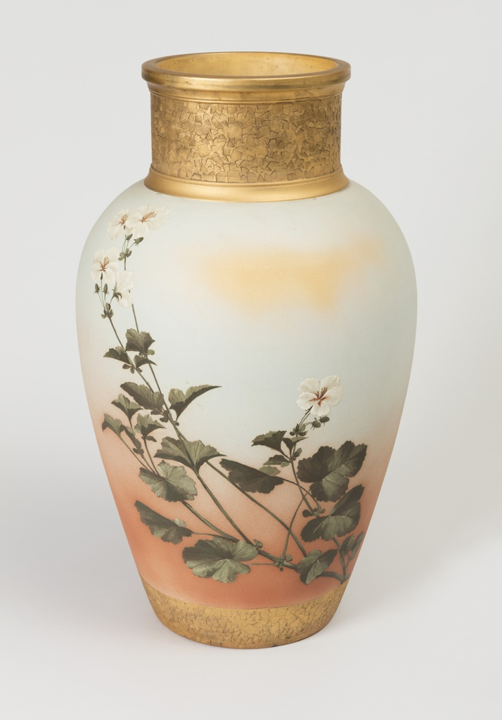 of baluster form, with peach glow matte background, painted with white dogwood blossoms on branches, the neck and foot gilded with a textured pattern of squares, the gilding going into the interior of the neck.