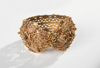 Cuff type bracelet, rococo scroll and trellis decoration, the underside with pierced zig-zag bands.