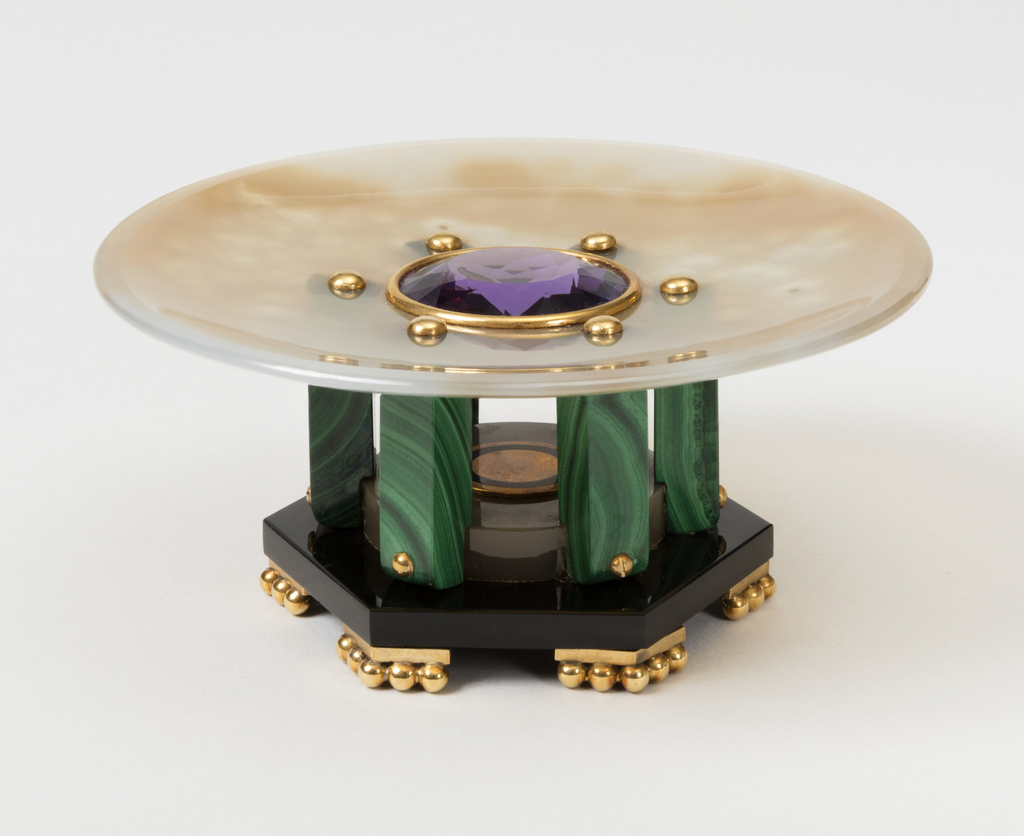 Circular chalsedony dish set with a gold mounted faceted circular amethyst surrounded by gold screw heads which hold the six rectangular malachite legs surrounding a chalcendoy disc surrounding a gold and enameled disk, all standing on an hexagonal base with six gold feet terminating in small spheres set at the angles.