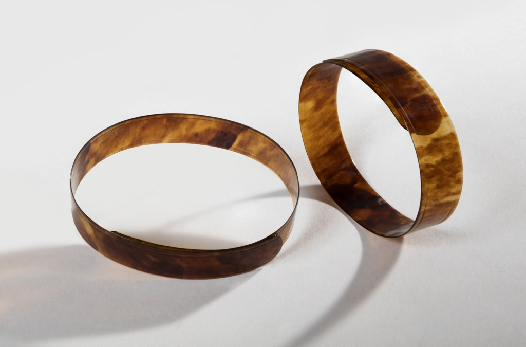 """Bands of tortoiseshell curved to form bracelets; tag attached reads: """"Pair of tortoise shell bracelets worn by Amy Hewitt (Mrs. J. O. Green oldest daughter of Mr. and Mrs. A.S. Hewitt) when a child."""""""