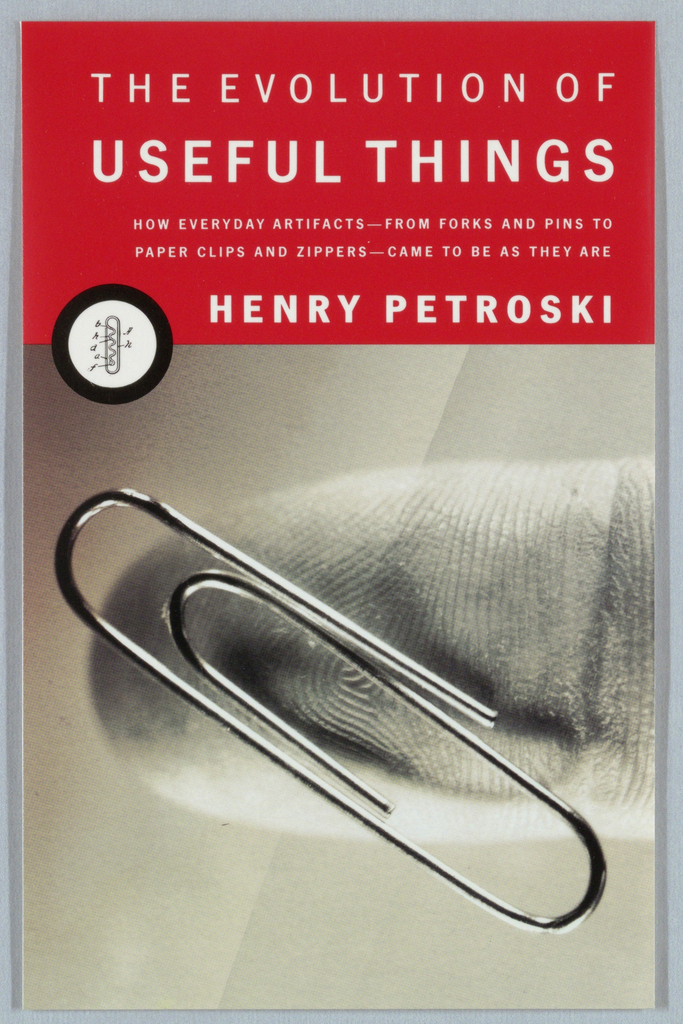 Book cover for The Evolution of Useful Things, by Henry Petroski, published by Alfred A. Knopf. Front cover bisected into halves with white text on red background at top and photoillustration with detail of paperclip on human fingertip at bottom. Along dividing line, at left, a white circle with thick black border with early paperclip patent illustration. Above, in white text: THE EVOLUTION OF / USEFUL THINGS / HOW EVERYDAY ARTIFACTS--FROM FORKS AND PINS TO / PAPER CLIPS AND ZIPPERS--CAM ETO BE AS THEY ARE / HENRY PETROSKI; on spine, Knopf colophon appears in the form of a patent drawing.