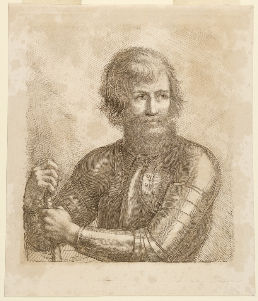 A bearded man in armor stands, facing frontally, gazing to the right, a staff in his hands.
