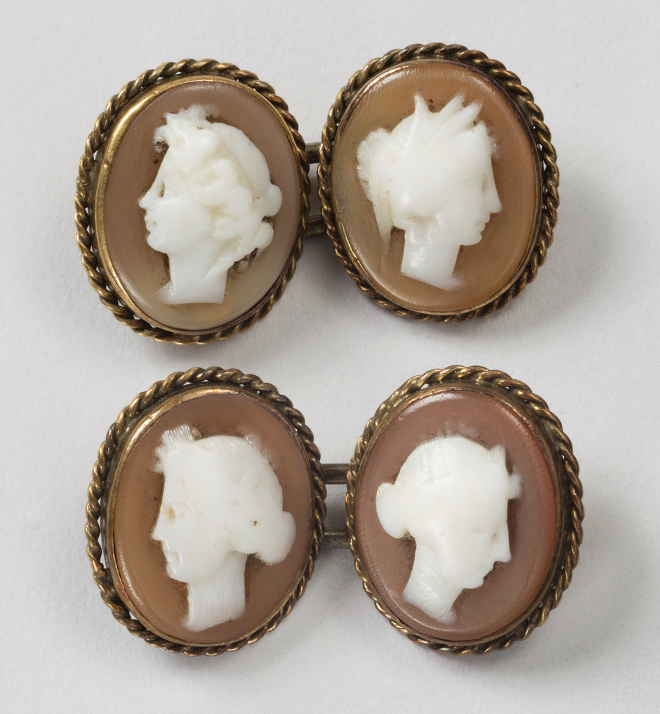 Shell cameos showing women's heads (white on brown) surrounded by gold in rope design and mounted on gold plates joined by gold links.