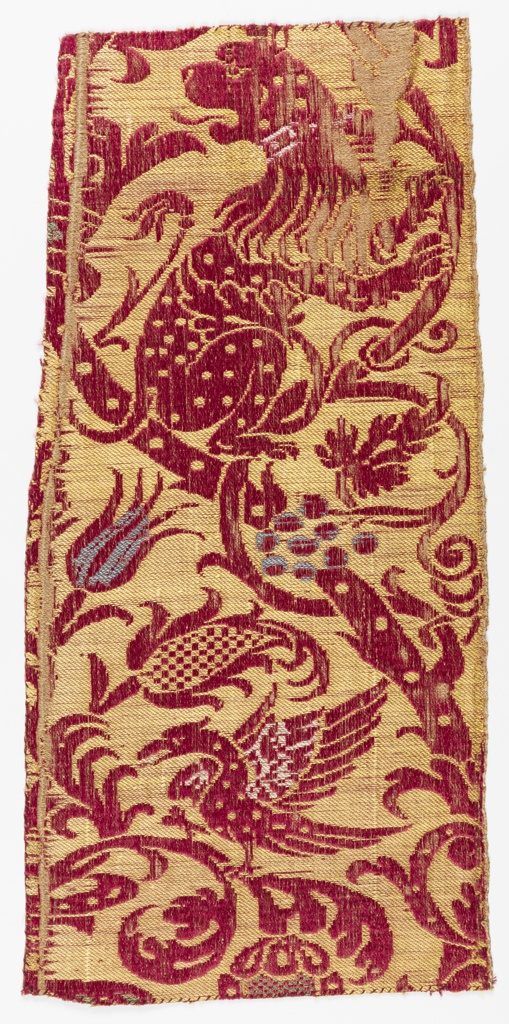 Fragment of woven fabric with a lion and bird of prey on a curving vine with exotic flowers and foliage, in red with touches of white and blue on a yellow background.