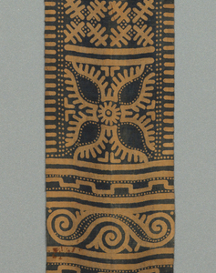 Long, narrow cloth patterned with panels of geometric and figural motifs, including the sacred buffalo at one end, in tan and indigo blue.