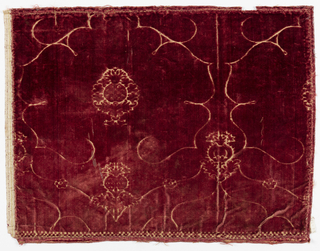 Deep red cut and voided velvet with a design of lobed medallions containing a central pineapple or pomegranate motif, in the linear style.