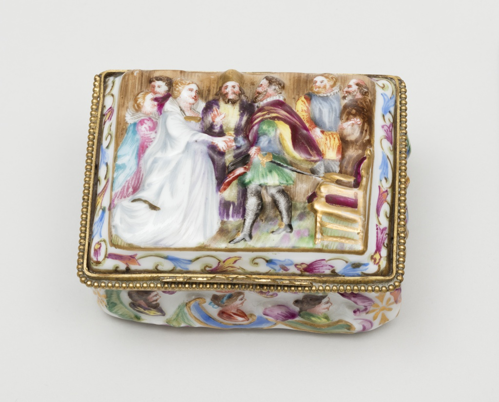 """Box, raised and colored decoration, heads & scrolls. Lid, raised and colored royal marriage scene; border, flat conventional flowers. """"Cappi di Monte"""""""