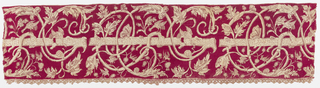 Border of natural linen, embroidered with red silk; the red outlines the details of the pattern but also fills in the background entirely. Central trunk entwined with wildly curving branches; flowers, birds and butterflies throughout. Trimmed on one long side with gold bobbin lace.