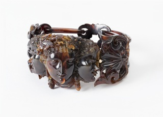 Dark brown tortoise shell with intricately carved center showing a frontal female head framed by two male profiles.