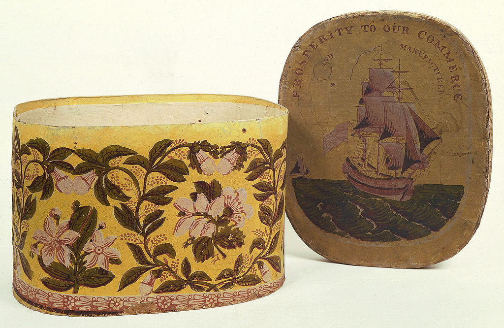 On box, large-scale floral sprig set within a vining foliate framework. On lid, sailing vessel on ocean, with legend: Prosperity to our Commerce and Manufacturers. Printed in pink, white and olive on a yellow ground.
