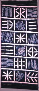 Length of cotton divided into a grid, with each square containing a geometric pattern. The white designs are created by resisting the indigo dye by sewing and tying sections of cloth with raffia thread. Traces of the raffia sewing thread are still present.