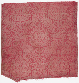 Red ribbed silk ground with a large-scale symmetrical palmette surrounded by four serrated leaves connected by a crown. The pattern is formed by one horizontal rib having an extra white silk weft and the alternating rib having a narrow strip of flat silver.