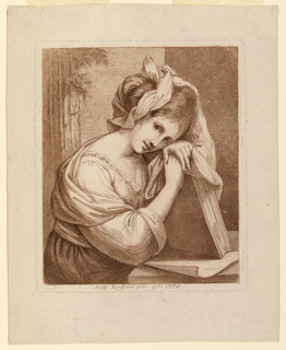 The artist sits at a table, resting her elbows on it, with her head on her hands, which are supoprted by a large book.