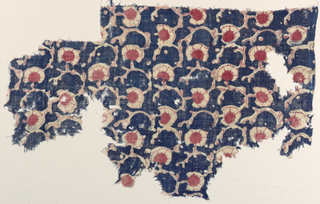 Fragment of tightly spun, loosely woven cotton plain weave with all over pattern of very simple scrolling stems, carnation-like flower heads reserved on deep blue ground, with accents and details painted in red.