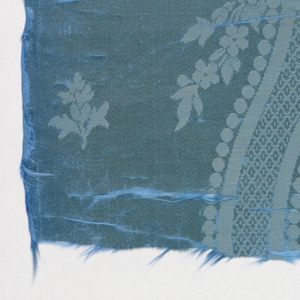 Oval panel in blue damask probably for a chair back with a design of an oval frame enclosing a floral group. Acanthus leaves and swags below frame.