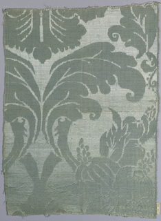 Light blue damask fragment with an incomplete design of a large-scale foliate ogive pattern with stylized floral and pomegranate forms.