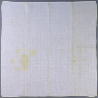 Two napkins of white linen damask, showing varying small scale patterns.