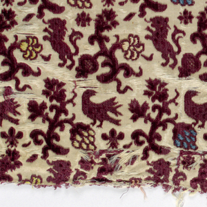 Cream-colored ground with pattern of pomegranate sprigs with rampant lions and birds.