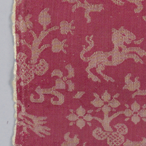 Red and green damask in a small, allover design of plants, lion and birds.