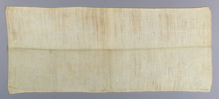 Length of undyed linen toweling with small overshot pattern. Two cloth selvedges. Narrow hand hem top and bottom in linen thread.