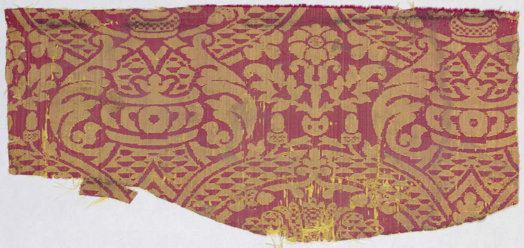 Incomplete large-scale design with circular motifs and acanthus foliage in red and yellow.