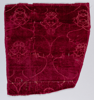 Deep red cut and voided velvet with a design of lobed medallions with central pineapple or pomegranate motifs in the linear style.