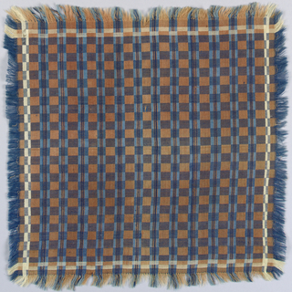 Small fringed napkin woven in a block design of brown, blue, tan and purple.