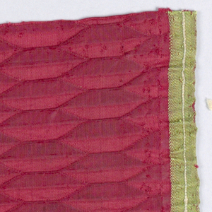 Dark red damask with an oblong shaped geometrical design. Green selvage.
