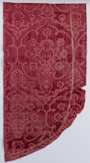 Pomegranates within lobed circles with floral decoration in red. Fragment was probably part of a chasuble at one time.