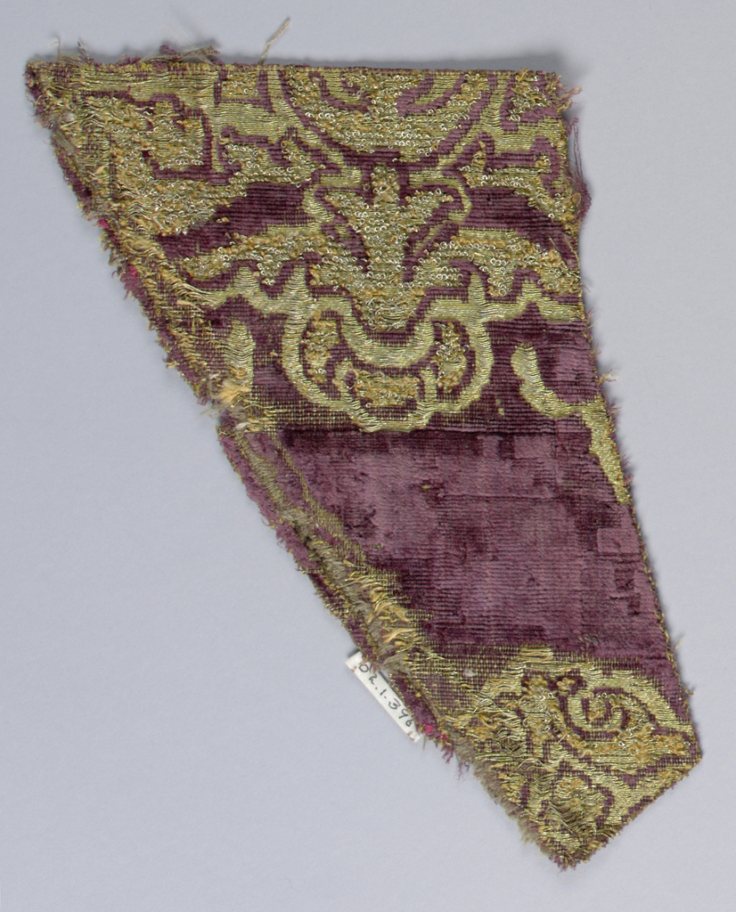 Incomplete pomegranate motif in dark mauve and gold on irregularly shaped piece.