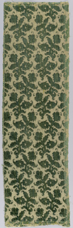 Panel of green silk velvet on yellow ground [in seven pieces], cut and uncut; pattern of floral spray.  Trimmed with tassel fringe.