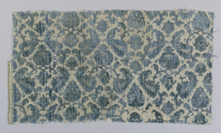 Fragment of green-blue cut and uncut velvet on a white ground shot with metallic thread in a leafy palmette and artichoke pattern.