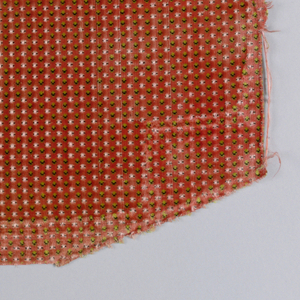 Fragments of velvet showing rows of tiny green and black dots of cut pile alternating with offset rows of tiny voided dots accented by floats of a supplementary weft on a rust red cut pile background.