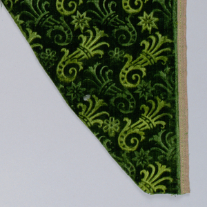Irregularly shaped green velvet with stamped pattern of diagonal floral shapes.