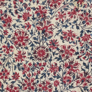 Small scale all-over floral vine pattern in black, red, and blue on an ivory ground.
