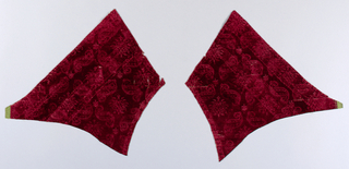 "Two shaped fragments of a stamped deep red cut velvet. Rows of offset flowers enclosed in detached ""S"" and ""Z"" curves which form a diagonal square grid."